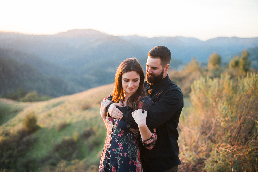 man with his arms wrapped around his fiance with the mountains in the background