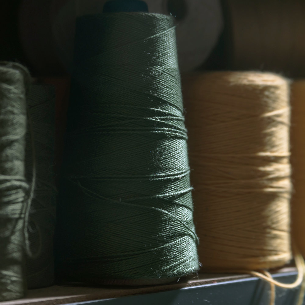 A spool of our hunter green cotton yarn