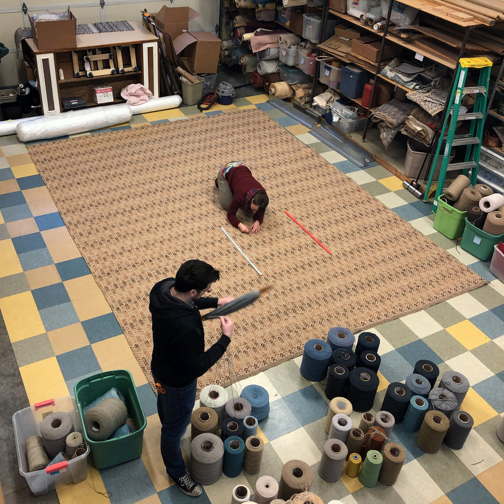 Cydni reviewing the front of the rug while Jeremiah winds shuttles for a blue and brown rug.