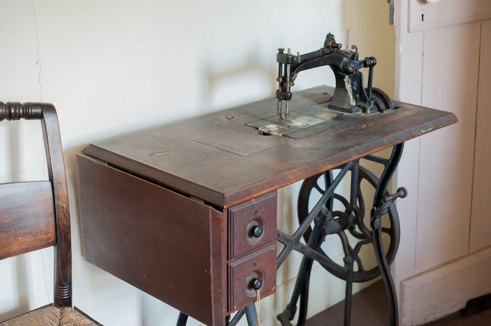 The sewing machine in the grandmother's room was controlled by the iron wheel and foot pedal.