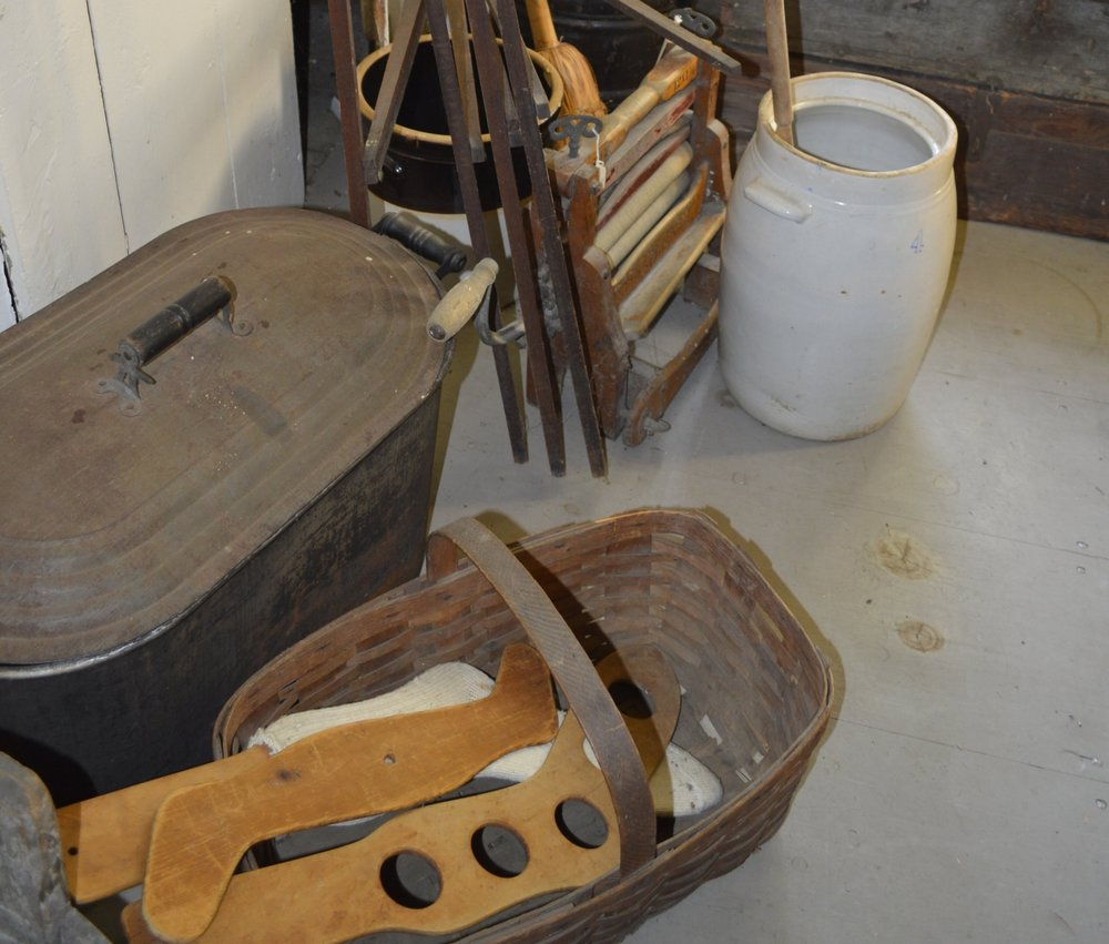 The wooden objects in the basket are sock stretchers. They prevented the wool from shrinking.