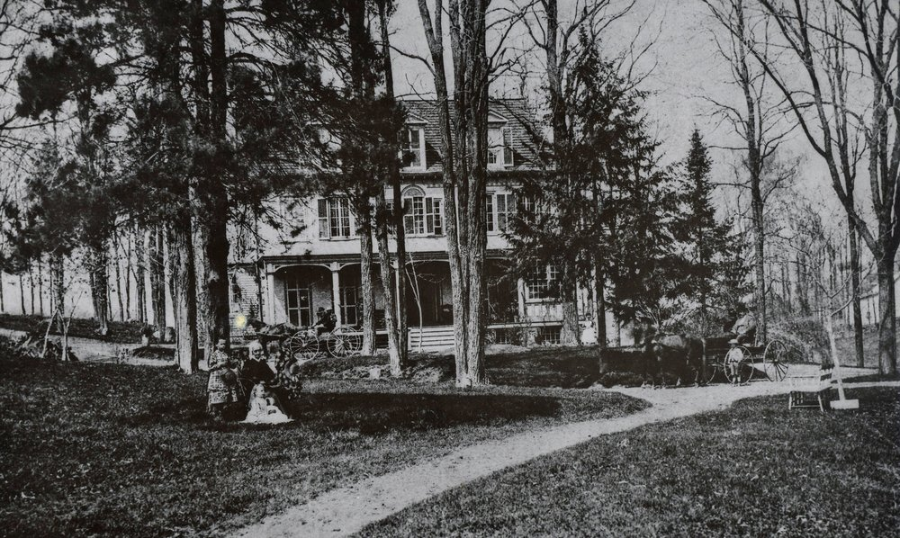 The Locusts, c. 1880s, in the foreground are Mrs. W. S. Popham and her granddaughters, Annie Popham and Emma. Emma later married Cornelius B. Fish. By the wagon on the right by a wagon are Lewis C. Popham and his son, Fleming. Four generations of Pophams lived in this house.