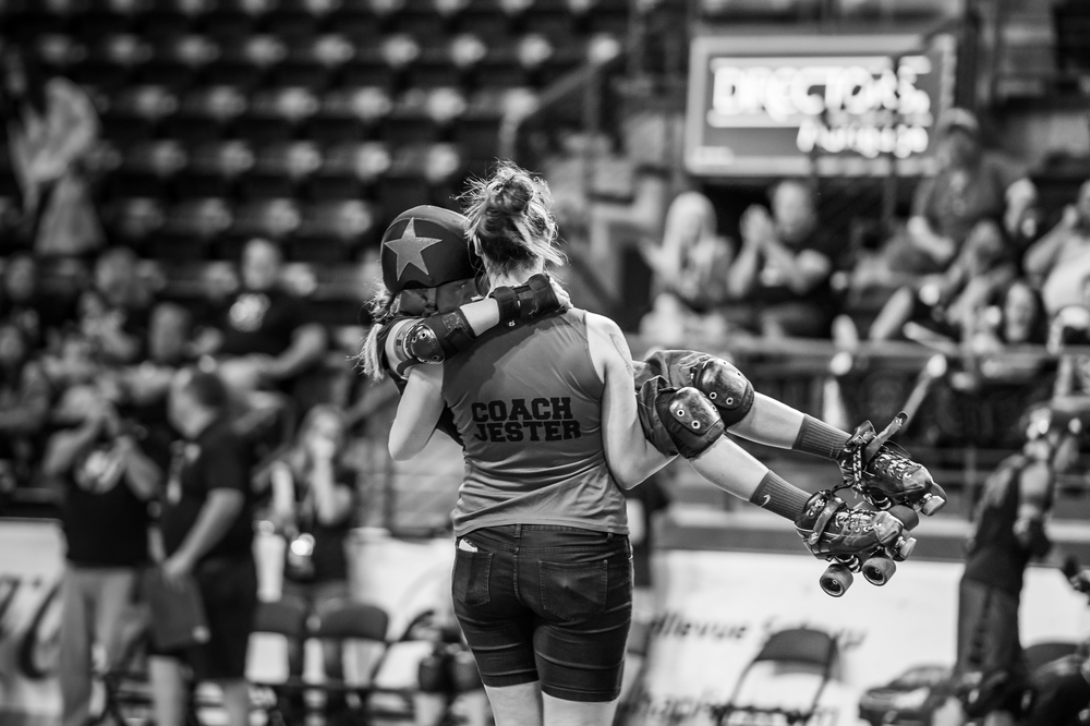 Jester helping M'n'M (of the Cherry Bomb Brawlers from Spokane) off the track after a bad fall, during the JRDA Championships - 2015