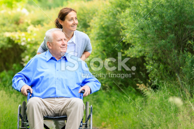 stock-photo-20635478-senior-man-sitting-on-a-wheelchair-with-caregiver.jpg