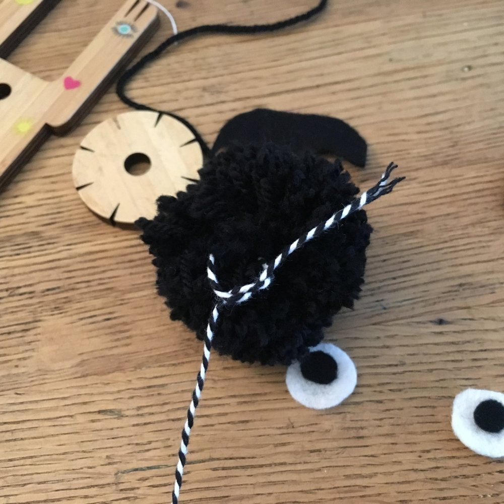 tie the string onto your pom pom bat to hang it up