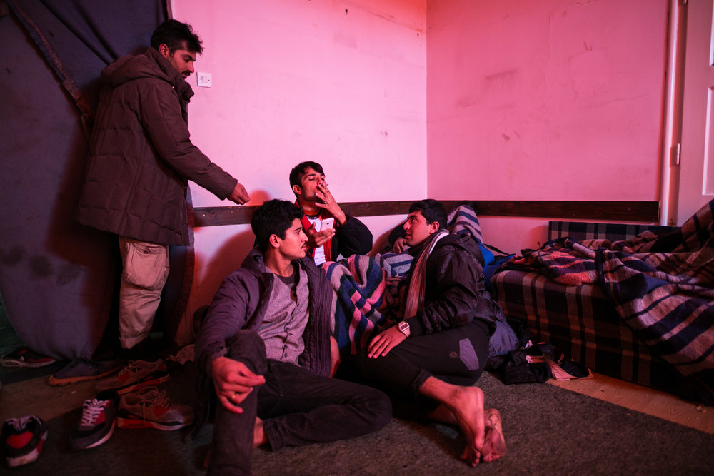 Amir shares a cigarette with other refugees from Pakistan. These young men did not know each other when they left their home country, but now stay together for safety. Belgrade, Serbia.