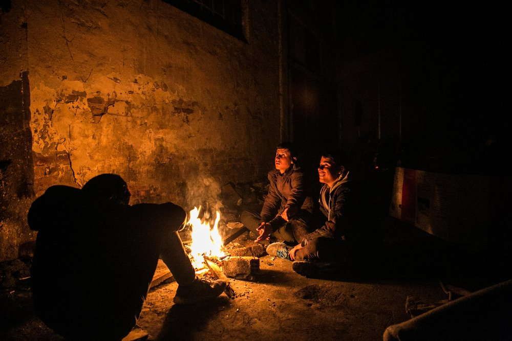 Unaccompanied minors trade stories around a fire inside the abandoned warehouse where they live with approximately 1,500 other male refugees. Belgrade, Serbia.