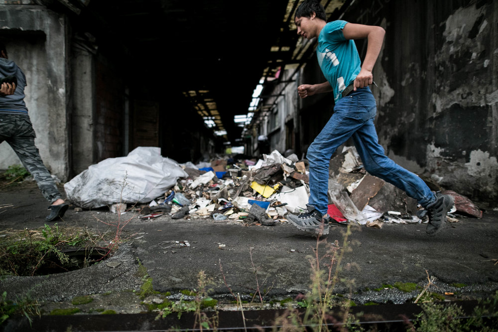 An unaccompanied minor runs past the latrine used by homeless refugees living in an abandoned warehouse in Belgrade, Serbia.