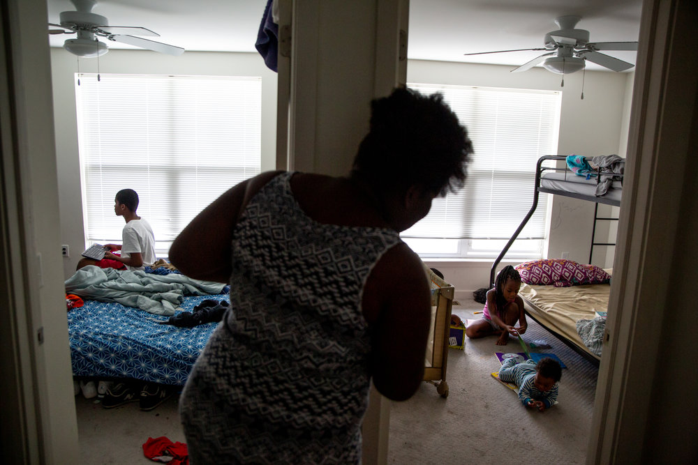 Mikelah looks in on her five-year-old sister, Justice Brooks, and son, Isaiah, at home in Columbus, Ohio, on Saturday, Oct. 20, 2018. In the other room, Mikelah's twelve-year-old brother, Tommy Hayes Jr., plays video games. Mikelah often watches over her siblings while her mom and stepdad are at work.