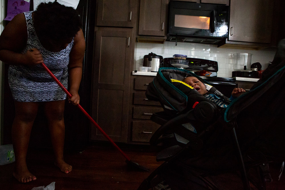 """Mikelah sweeps the kitchen floor next to her son, Isaiah, on Saturday, Oct. 20, 2018. """"I'm like the second mom in here,"""" Mikelah says of her responsibilities around the house and taking care of her siblings. Mikelah's stepfather works nights and sleeps during the day, when her mother works as a city bus driver."""