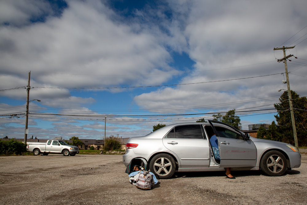 """""""I kind of miss having him in my belly,"""" Mikelah says, """"sometimes I have phantom kicks."""" Isaiah sits outside in the parking lot of New Generation Church on Sunday, Oct. 21, 2018, while Mikelah finishes talking to her cousin, Lisa Fleming, 18, in the front seat of Lisa's car."""