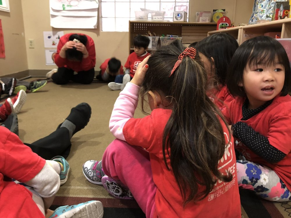 A teacher demonstrates how to protect one's self in an earthquake to the children at Wu Yee Children's Services Lok Yuen Child Development Center
