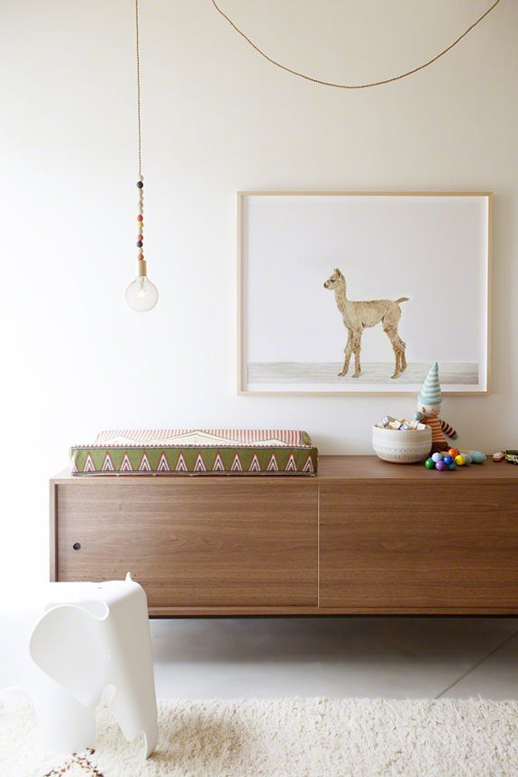 This mid -century modern floating credenza adds a sophisticated touch to a simple, yet playful room.