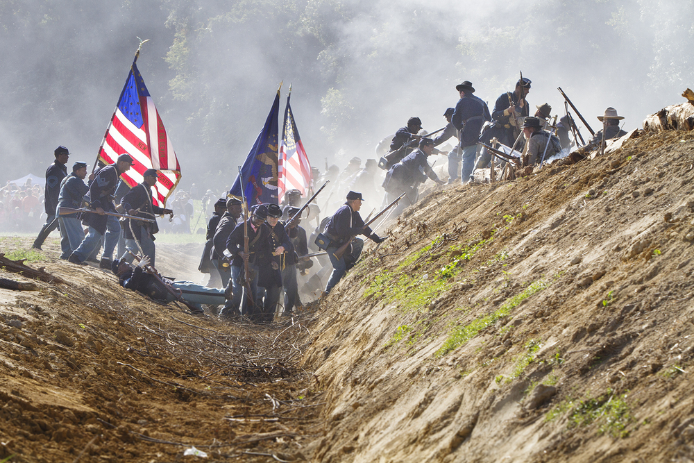 Union troops, including USCT, overrun a Confederate position during a reenactment of the battle of New Market Heights. Henrico, Co., Virginia, September 2014