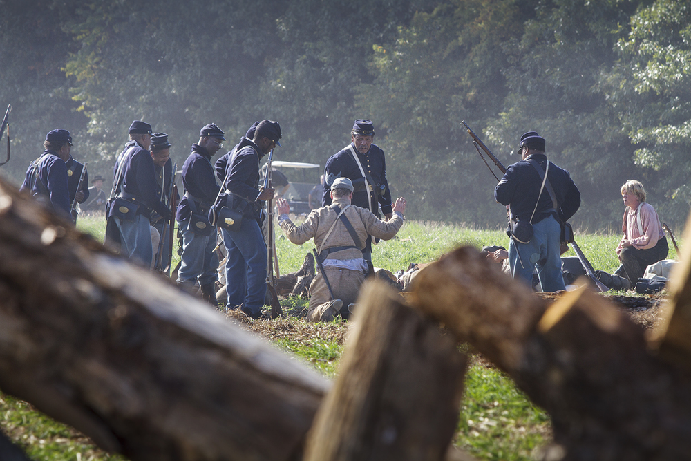 Soldiers of the United States Colored Troops take a Confederate prisoner during a reenactment of the battle of New Market Heights. Henrico, Co., Virginia, September 2014