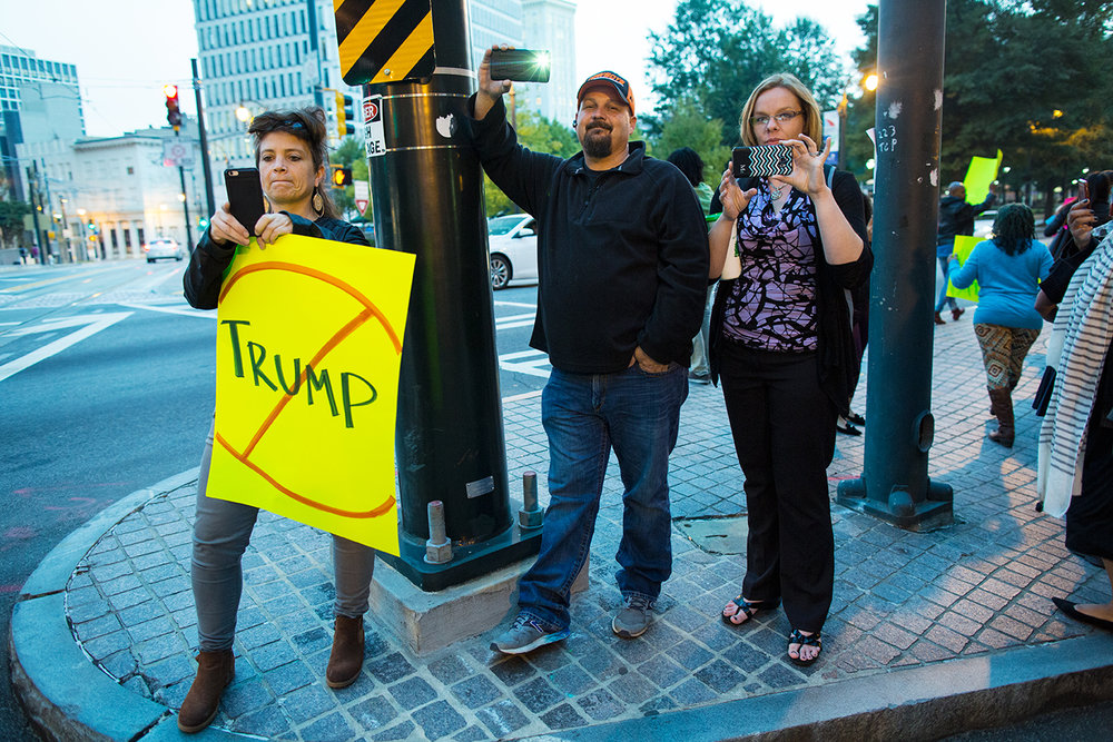 Anti-Trump protester and bystanders photograph march held during the Facing Race 2016 conference against president-elect Donald Trump, who gave voice to  bigotry  and  encouraged violence  during his campaign. Atlanta, GA, 10 November