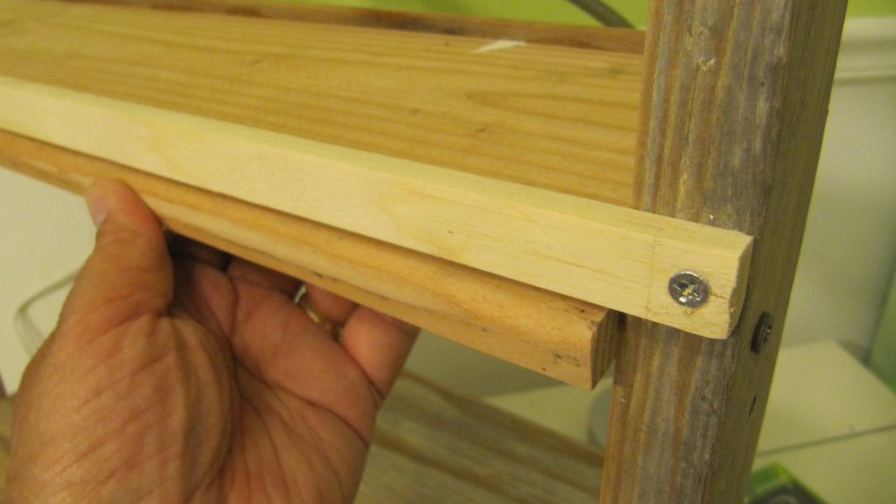 A wooden strip across the back also keeps the shelf in place and keeps things from falling off.