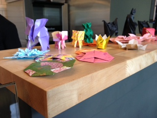 The décor includes a miniature origami menagerie.