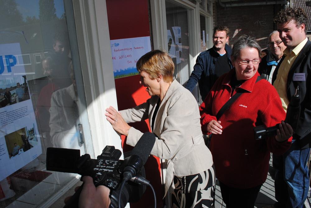Een Zaanse wethouder opent een tentoonstelling in ons tijdelijke kantoor in een gedeeltelijk afgebrand winkelcentrum.