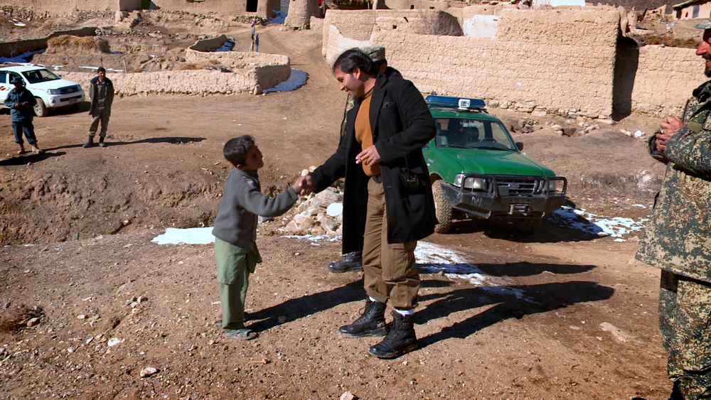 Qadir Temori, shaking hands with the son of one of Mes Aynak's brave workers.