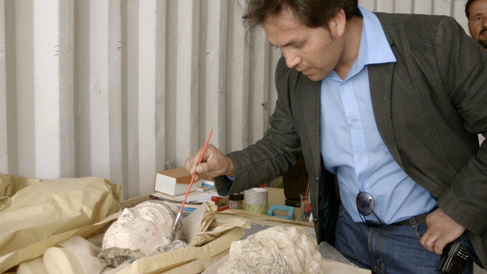 Lead archaeologist Qadir Temori, cleaning pieces of one of Mes Aynak's Buddha statues.
