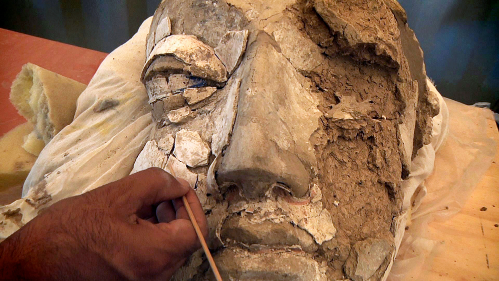 An archaeologist cleaning the face of a giant Buddha statue.