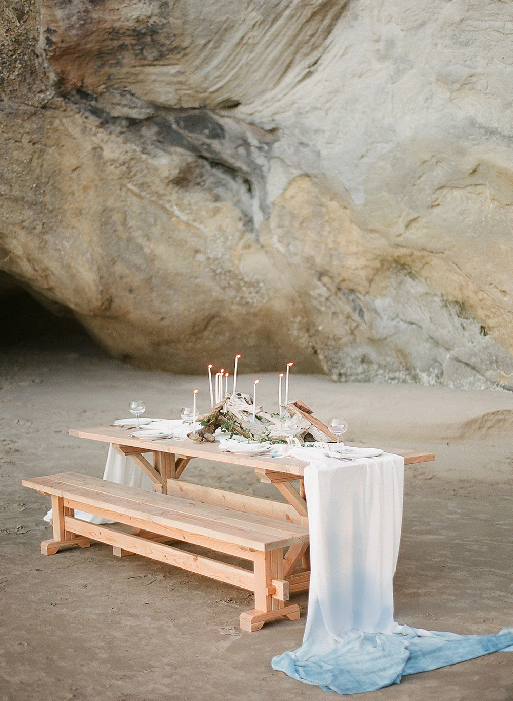 coastal tablescape with indigo dip-dyed fabric and driftwood centerpiece with skinny taper candles at this coastal wedding in Oregon Coast Wedding photographed by Destination Wedding Photographer- Lexia Frank - a film photographer for luxury weddings in oregon. TOP DESTINATION WEDDING PHOTOGRAPHY, OREGON COAST WEDDING, WWW DOT LEXIA FRANK DOT COM