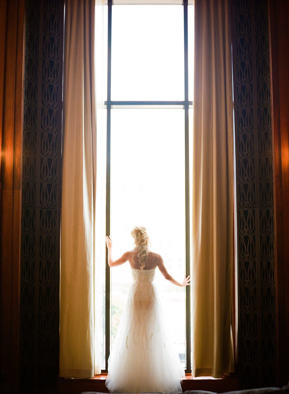 top destination wedding photographer Lexia Frank photographs the wedding of NFL football star Green Bay Packer Bryan Bulaga's wedding at the hilton in milwaukee as the bride stands in the doorway