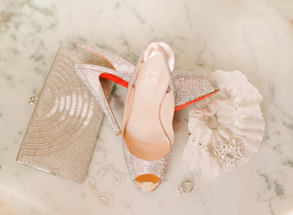 DESTINATION WEDDING PHOTOGRAPHER LEXIA FRANK PHOTOGRAPHS PRO FOOTBALL PLAYER BRYAN BULAGA OF THE GREEN BAY PACKERS WEDDING AT THE HILTON CITY CENTER IN DOWNTOWN MILWAUKEE. PICTURED ARE THE BRIDE'S GORGEOUS VINTAGE RING, CHRISTIAN LOUBOUTIN WEDDING SHOES, WEDDING PURSE AND GARTER ON MARBLE