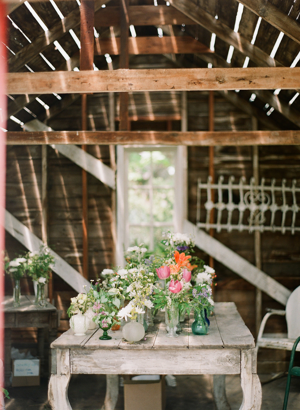 mis-matched vases for wedding flower center pieces wait in a barn while Destination Wedding photographer Lexia Frank photographs this springtime wedding on film at the Northwind Perennial Gardens in wisconsin