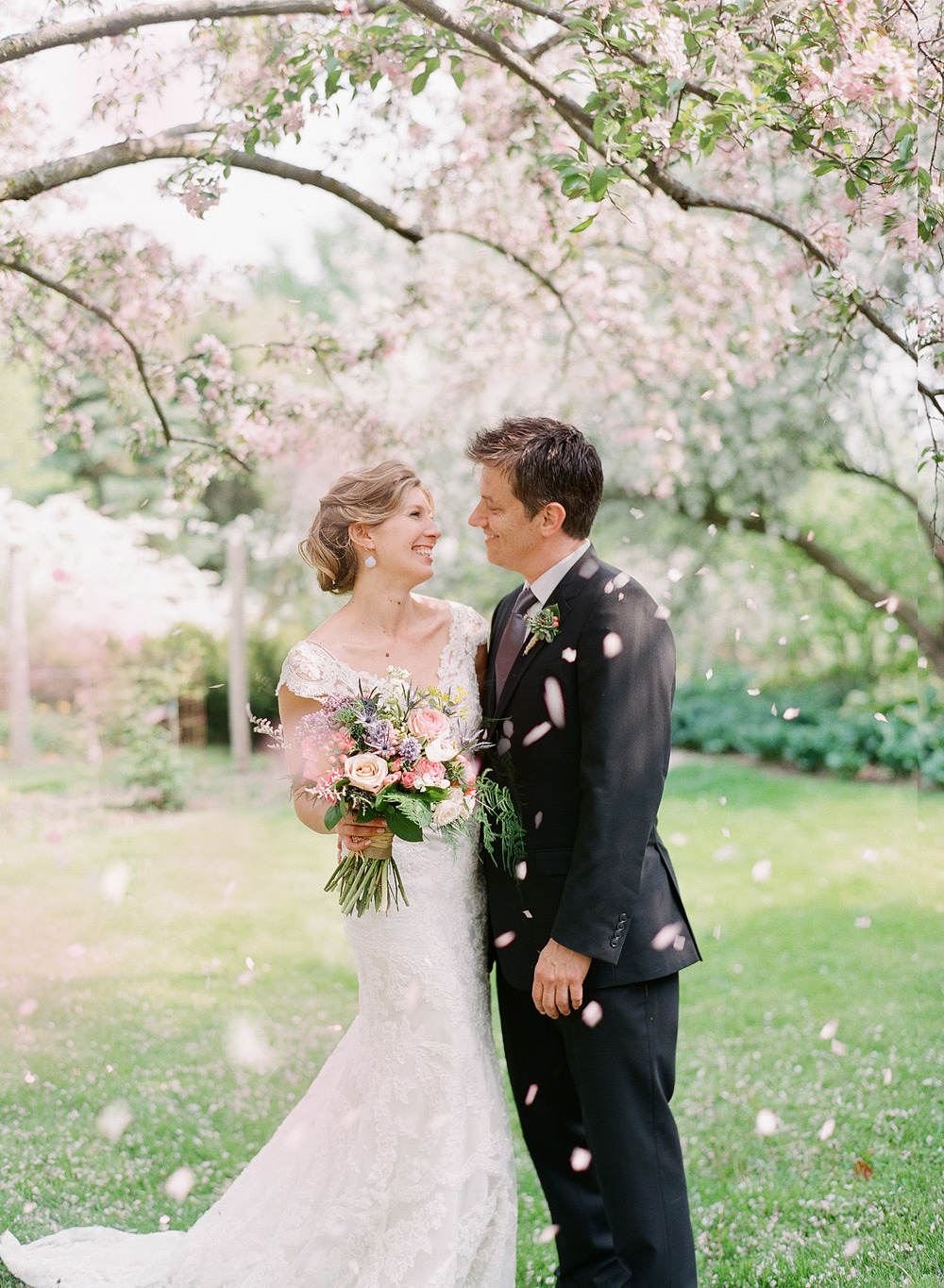 bride and groom have their first look under falling petals at their wedding at Northwind Perennial Gardens in wisconsin while destination photographer Lexia Frank photographs on film