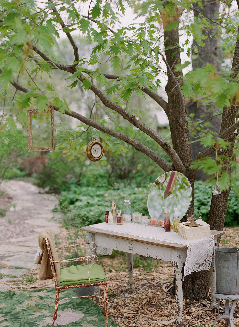 bride gets ready outside at a vintage table at the Northwind Perennial Gardens in Wisconsin while Destination Wedding Photographer Lexia Frank photographs in film
