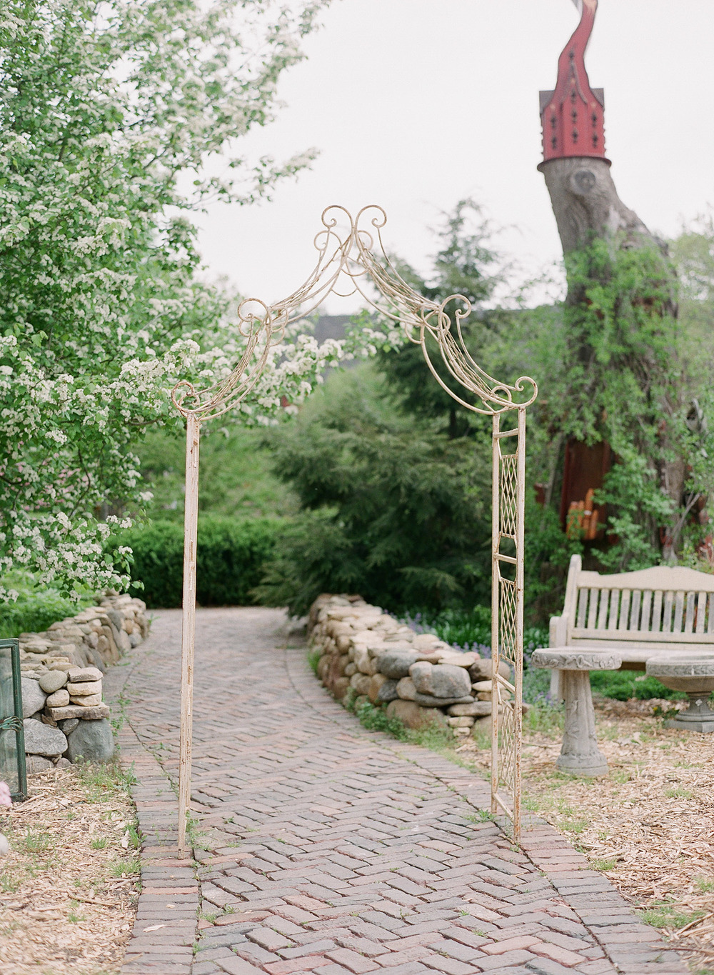 a wrought iron garden archway and brick path leading to a whimsical birdhouse at this springtime wedding at the Northwind Perennial Gardens in wisconsin while Destination Wedding Photographer Lexia Frank photographs the wedding on film