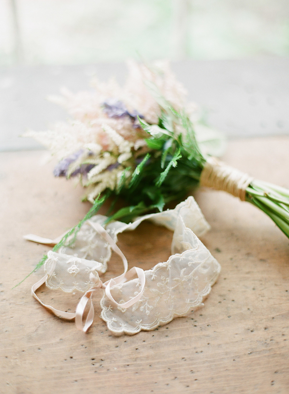 a bouquet and vintage lace garter sit on a table at this springtime wedding at Northwind Perennial Gardens in Wisconsin while Destination Wedding Photographer Lexia Frank photographs this wedding on film