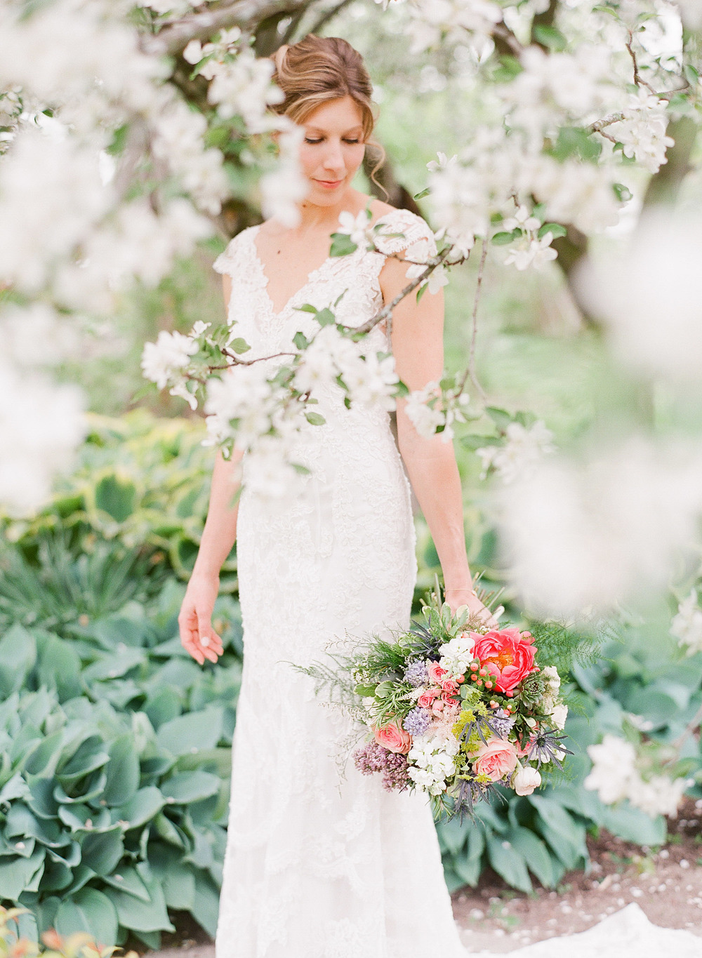 the bride stands among blooming trees and hostas holding her asymmetrical bouquet of ranunculus peonies terms lavender and roses at her springtime wedding at Northwind Perennial Gardens - a beautiful wisconsin wedding venue-  while Destination Wedding Photographer Lexia Frank photographs her wisconsin wedding on film
