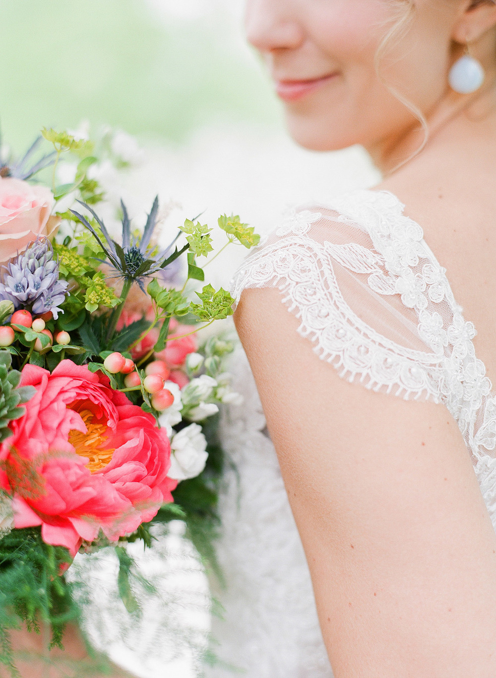 bride wears a vintage lace dress with cap sleeves and holds her asymmetrical bouquet of peonies ranunculus and ferns at her springtime wedding at Northwind Perennial Gardens- a beautiful Wisconsin Wedding venue- while Destination Wedding Photographer Lexia Frank photographs her wedding on film