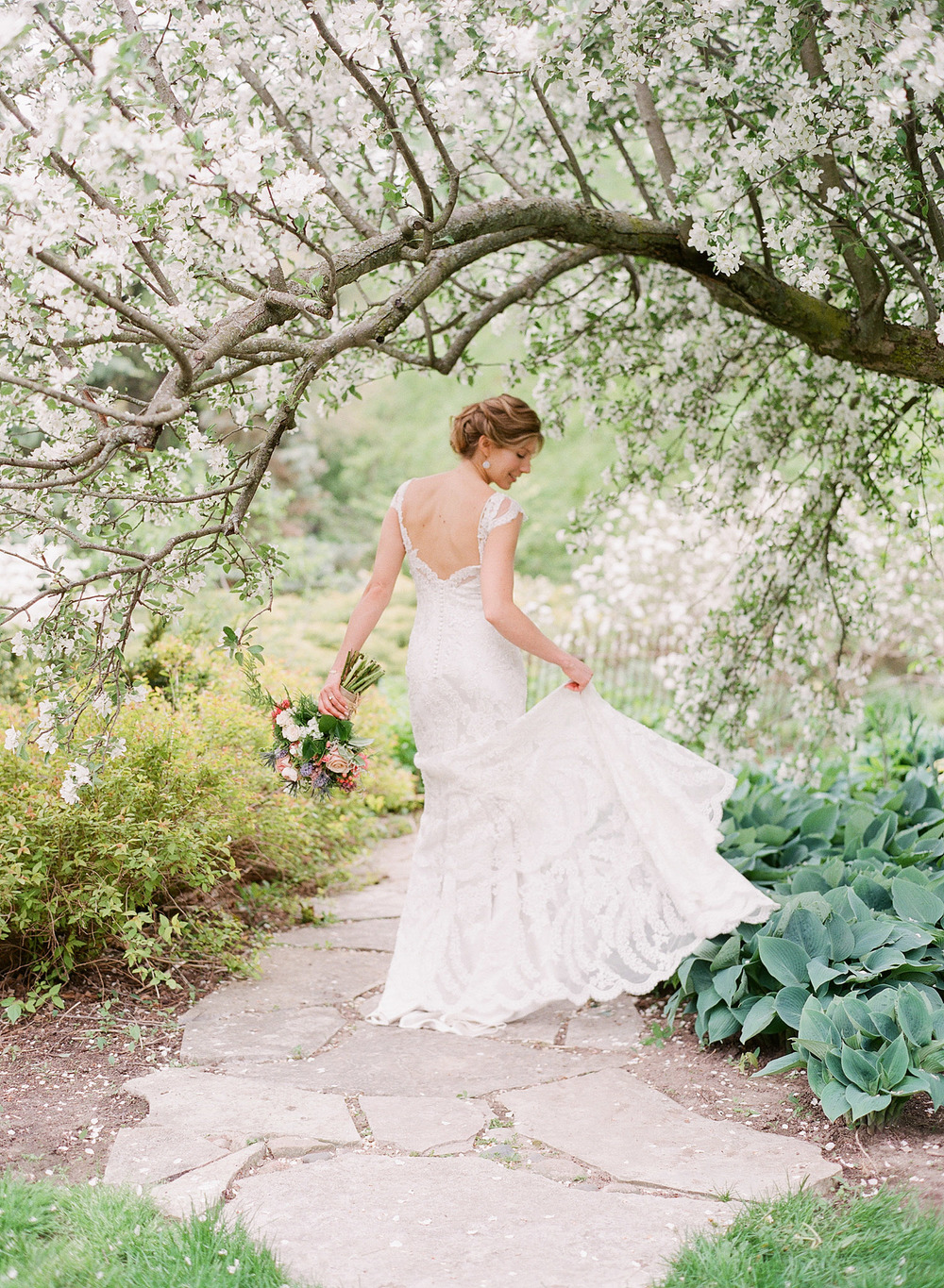 bride twirls her lace wedding dress with cap sleeves under blooming trees at her springtime wedding at Northwind Perennial Gardens - a beautiful wisconsin wedding venue - while destination wedding photographer Lexia Frank photographs her wedding on film