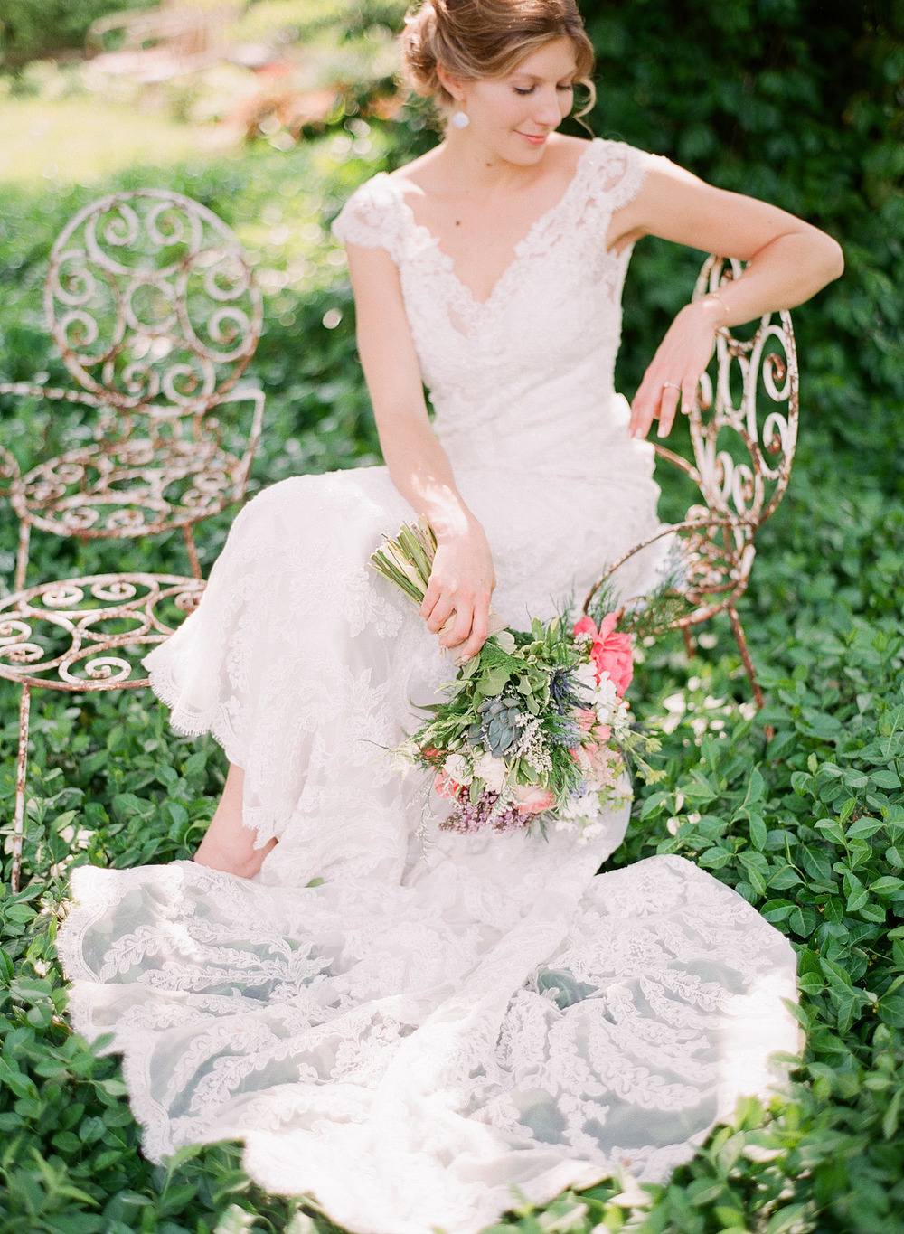 bride sits on vintage wrought iron chair in ivy in her vintage lace wedding dress with cap sleeves holding her asymmetrical spring wedding bouquet at this  springtime wedding at Northwind Perennial Garden - a beautiful wisconsin wedding venue - while Destination wedding photographer Lexia Frank Photographs this wedding on film