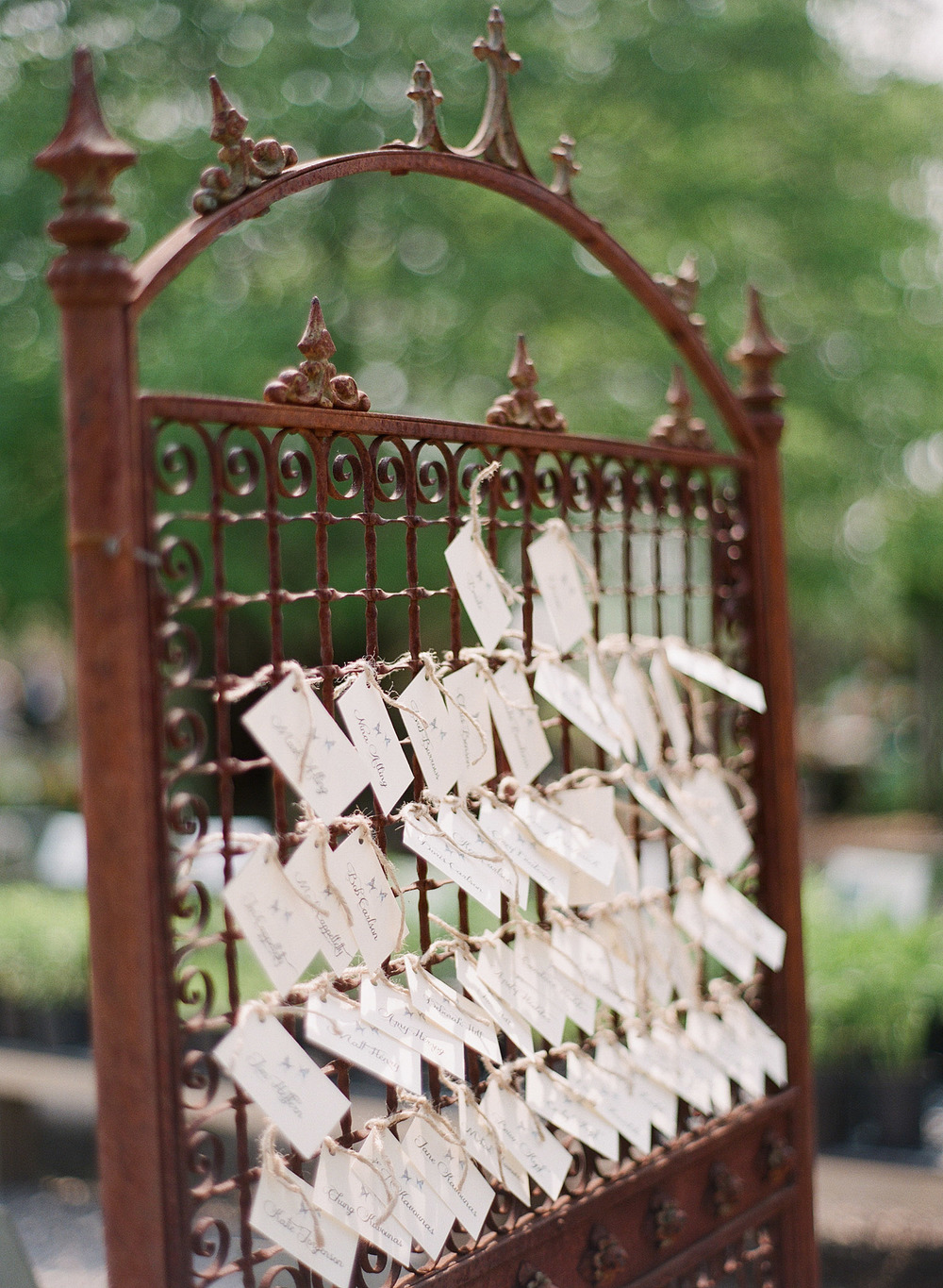 genius escort card ideas- these escort cards hang on a gate at the entrance to the reception at this  springtime wedding at Northwind Perennial Garden - a beautiful wisconsin wedding venue - while Destination wedding photographer Lexia Frank Photographs this wedding on film