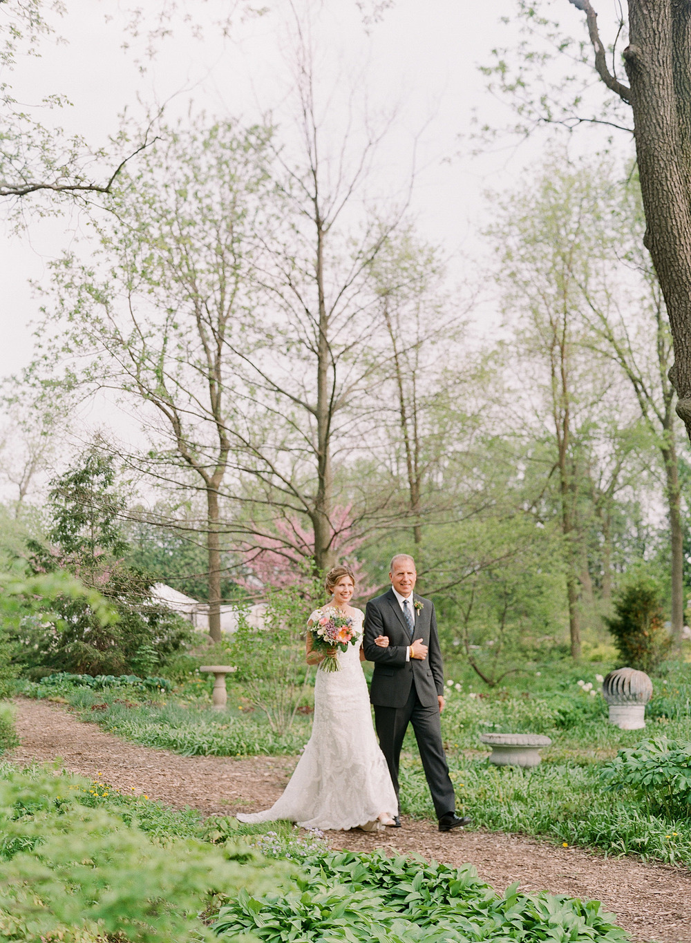 father walks bride down the aisle at this springtime wedding at Northwind Perennial Garden - a beautiful wisconsin wedding venue - while Destination wedding photographer Lexia Frank Photographs this wedding on film