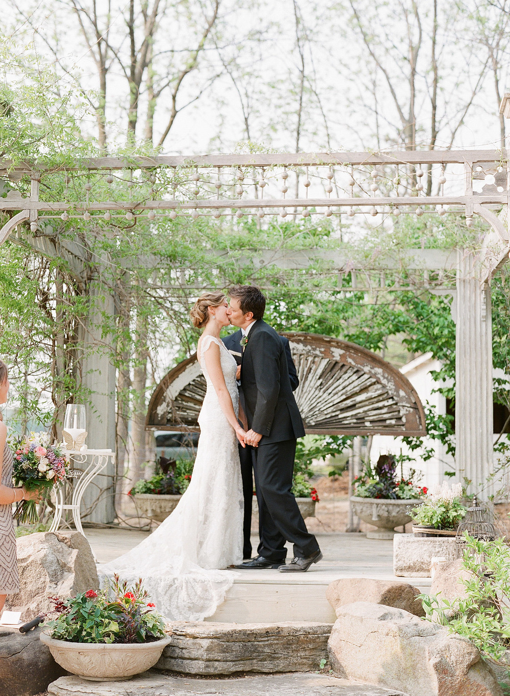 bride and groom kiss at the ceremony at this springtime wedding at Northwind Perennial Garden - a beautiful wisconsin wedding venue - while Destination wedding photographer Lexia Frank Photographs this wedding on film