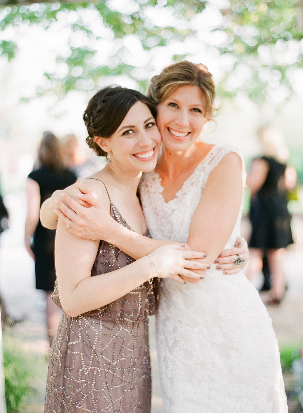 bride hugs bridesmaid at this  springtime wedding at Northwind Perennial Garden - a beautiful wisconsin wedding venue - while Destination wedding photographer Lexia Frank Photographs this wedding on film