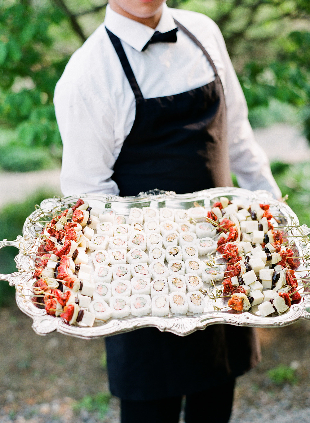 hors d'oeuvres of sushi are served at the cocktail hour of this springtime wedding at Northwind Perennial gardens - a wisconsin wedding venue - as a film wedding photographer Lexia Frank photographs this destination wedding on film