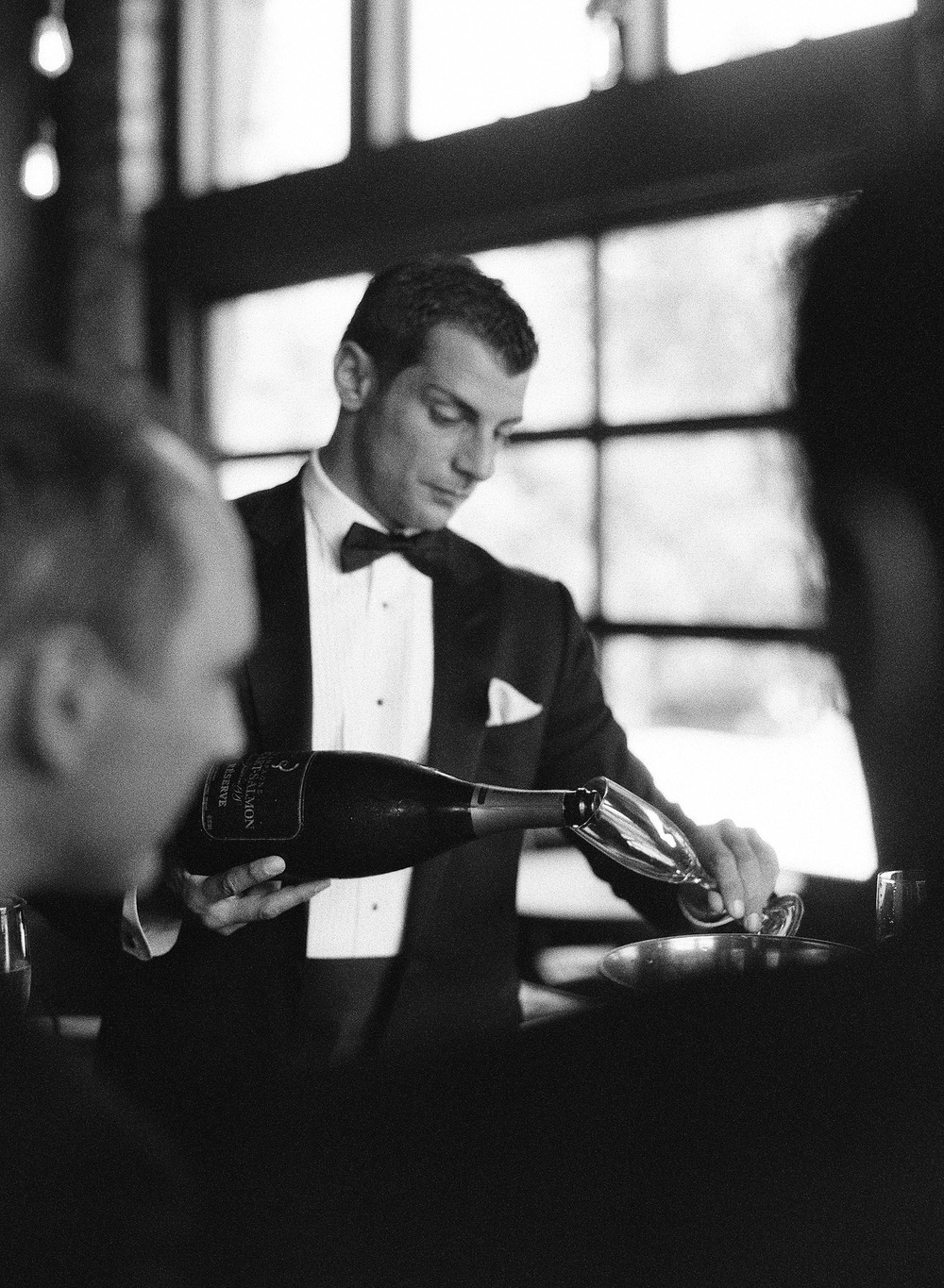 groom pours a glass of champagne for the groomsmen before his ceremony at the Italian villa named Villa Terrace where Destination wedding photographer Lexia Frank photographs this Italian destination Wedding entirely on film