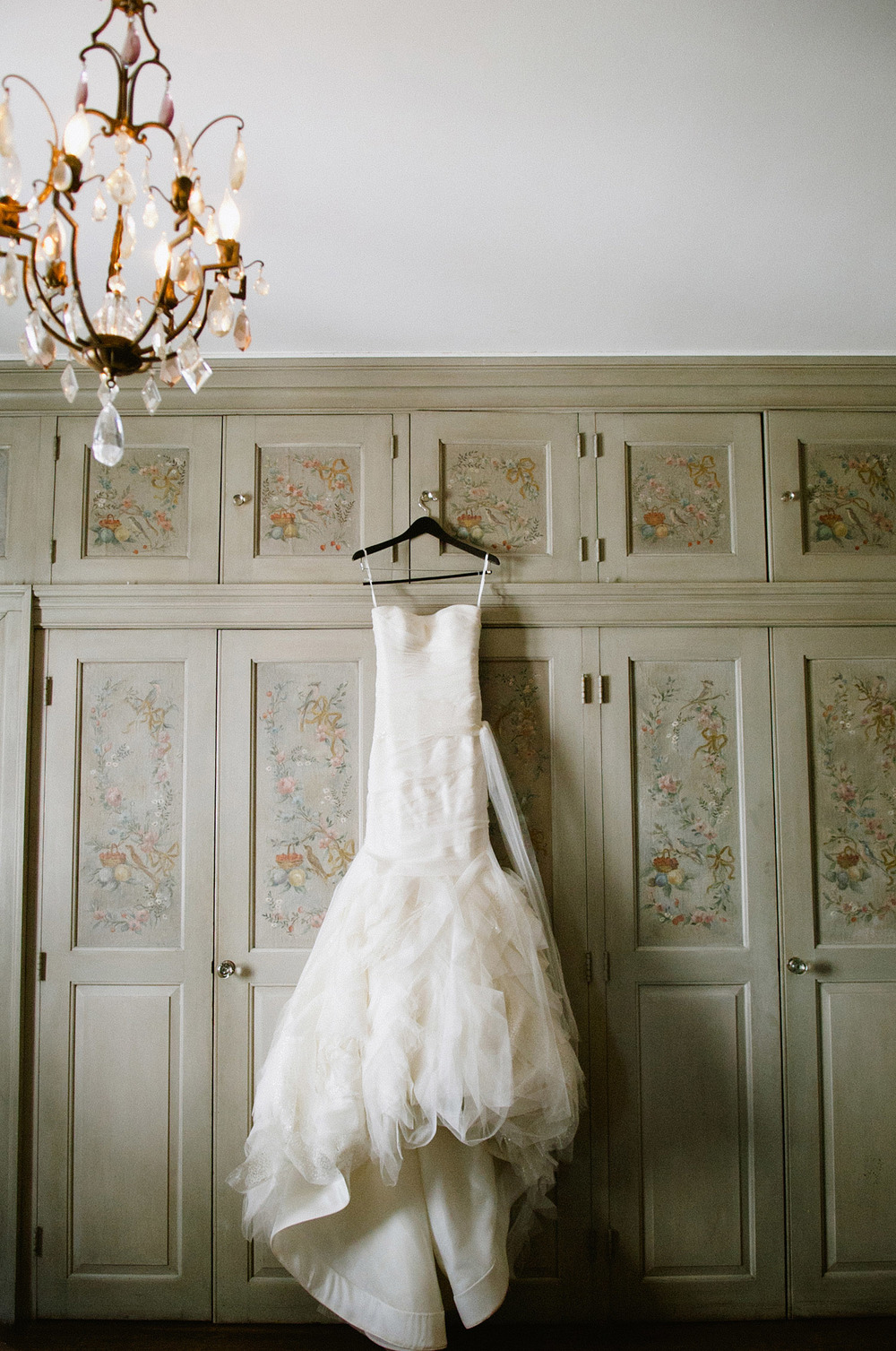 the wedding dress hangs in one of the rooms at the italian villa The Villa Terrace where Destination wedding photographer Lexia Frank photographs this italian destination wedding entirely on film as she is a wedding film photographer