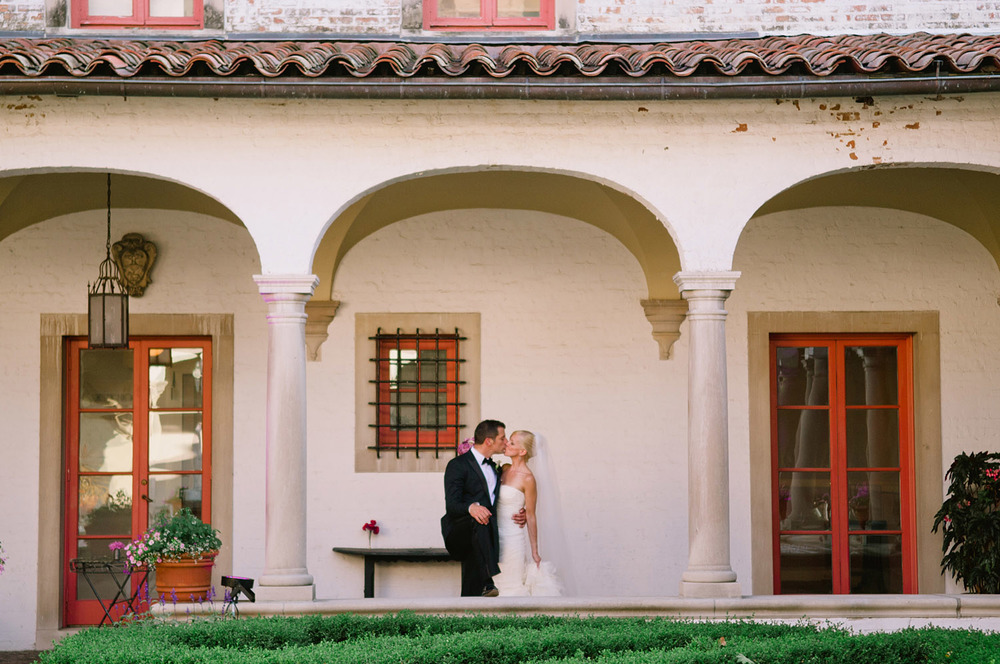 bride and groom kiss between columns at the italian villa during their destination Italian wedding at the Villa Terrace while destination wedding photographer Lexia Frank photographs their wedding on film