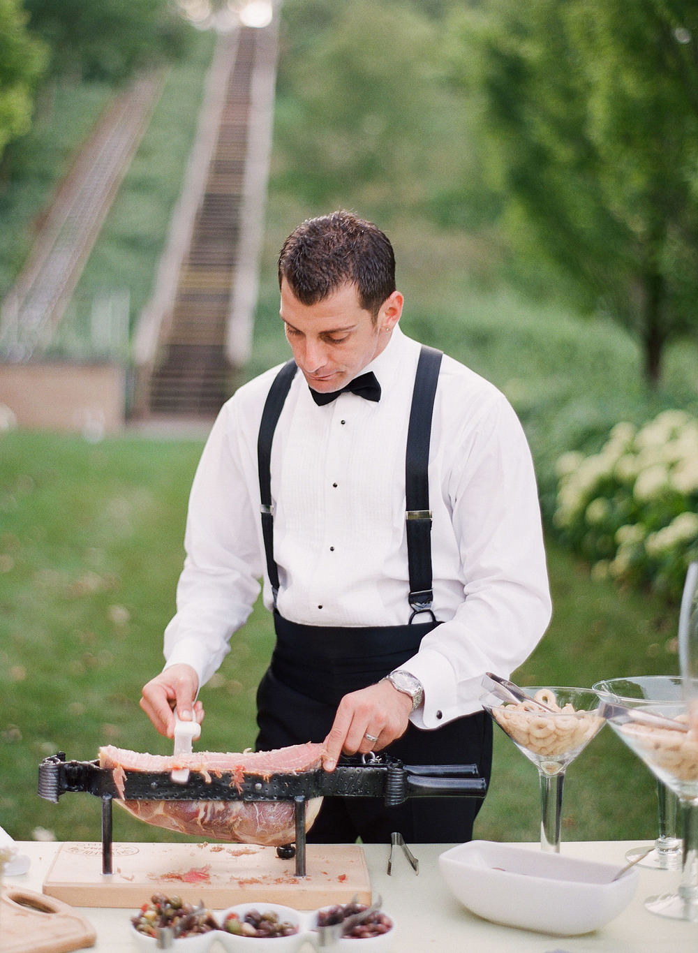 the groom cuts some prosciutto for the wedding day hors d'oeurves at the Italian wedding at the Villa Terrace, an Italian villa for weddings while Destination WEdding Photographer, Lexia Frank, photographs the wedding on film