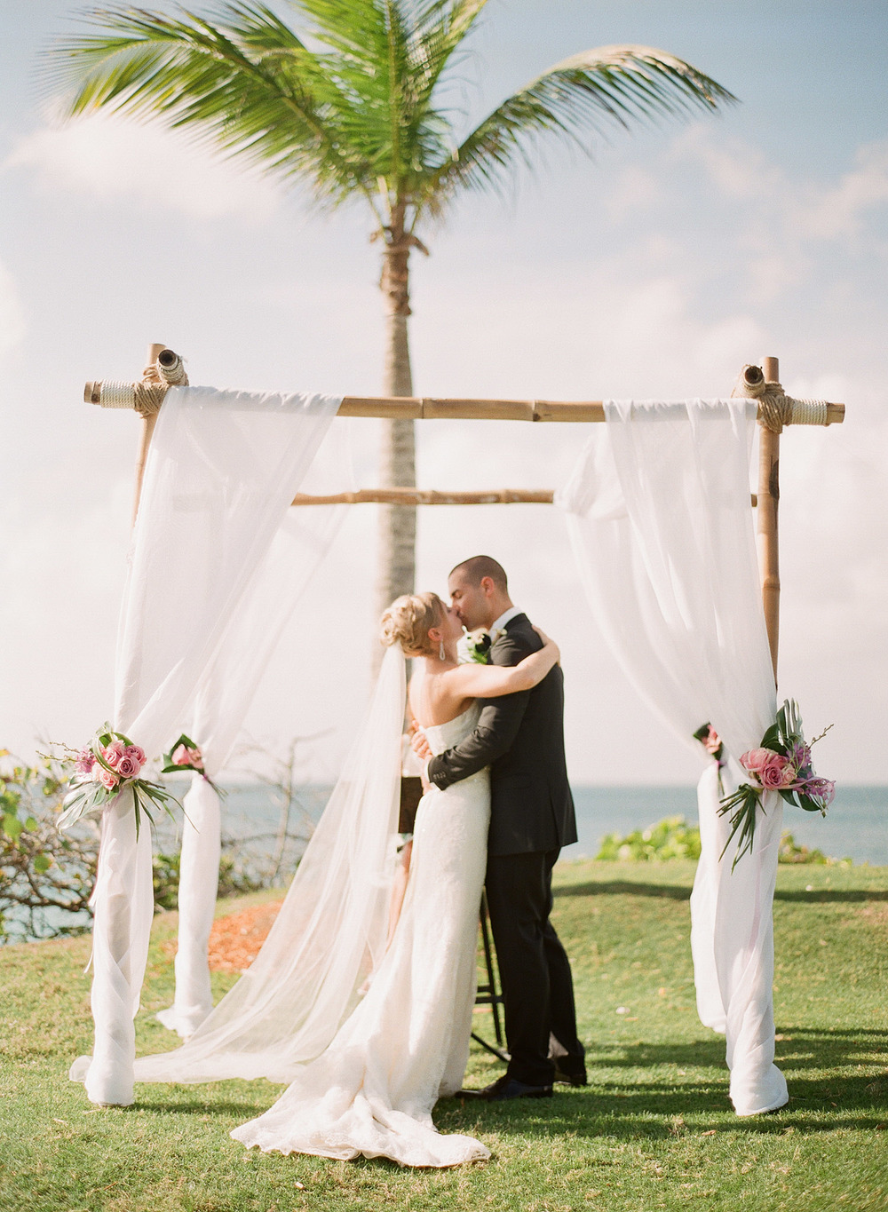 bride and groom kiss under their bamboo chuppa at their Vieques Island Wedding at the W hotel while Destination wedding photographer Lexia Frank photographs their wedding on film