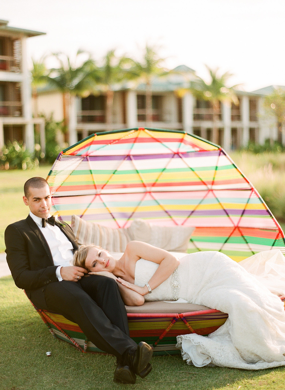 Destination Wedding Photographer Lexia Frank photographs this beautiful modern Vieques Island Wedding at the W hotel off the coast of Puerto Rico-  bride and groom lounge in a modern neon lounge chair on the beach as lexia photographs the wedding on film
