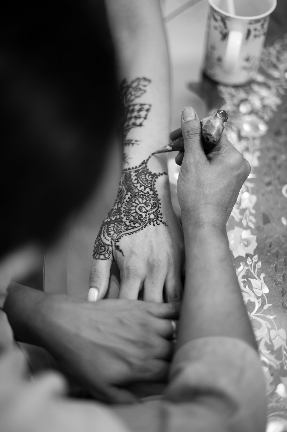 Top indian wedding photographer, Lexia frank, photographs this destination indian wedding in palm coast florida at the hammock beach resort indian wedding during the bride's mehndi ceremony as her henna artist does a beautiful minimalist mehndi design on her hands while Destination wedding photographer Lexia Frank photographs this luxury indian wedding in florida on film as she is a film photographer for indian weddings